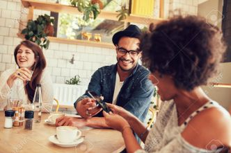 56098114-Portrait-of-young-friends-talking-in-cafe-and-looking-at-the-photos-on-smart-phone-Happy-young-peopl-Stock-Photo.jpg